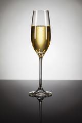 ein glas mit champagner auf schwarzem spiegel mit spot licht