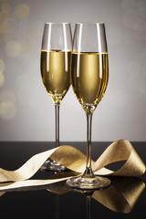 zwei gläser sekt mit goldenem band auf einem spiegel