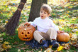Surprised little boy with halloween pumpkins and a broom sitting