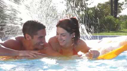 Couple Relaxing On Airbed Together In Swimming Pool
