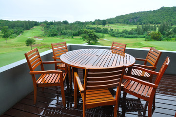 Chairs and table on wooden in a Green grass on a golf field