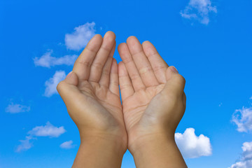 hand with blue sky and clouds