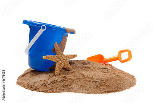 A blue pail and orange shovel with a starfish on the beach