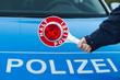 Polizist hält kelle vor Polizeiauto