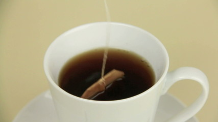 Electric jug then dipping a tea bag in a mug.