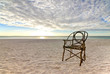 Old Bamboo Chair on Sandy Beach with Sunset