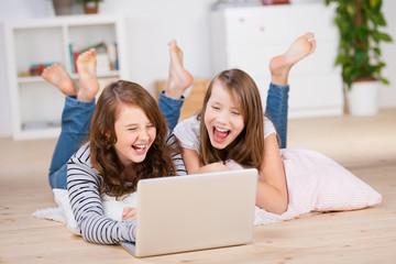 zwei lachende mädchen schauen auf den laptop