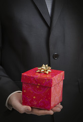 Man in suit holding a present close up