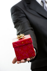 Man in suit giving a present close up