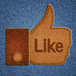 Like sign. Leather Thumbs up symbol on blue jeans background