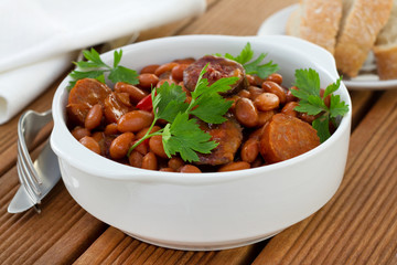 beans with sausages and sauce in the white bowl
