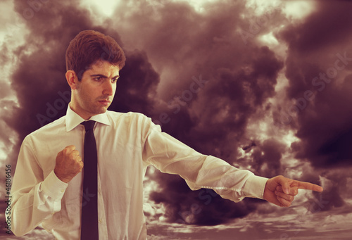 Angry Businessman with stormy clouds on background