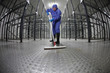 worker in protective  uniform cleaning floor in empty storehouse