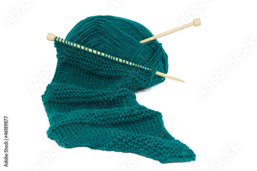 Scarf on knitting needles with a ball of wool