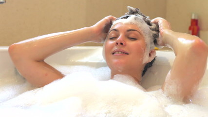Woman Washing Hair In Bubble Filled Bath