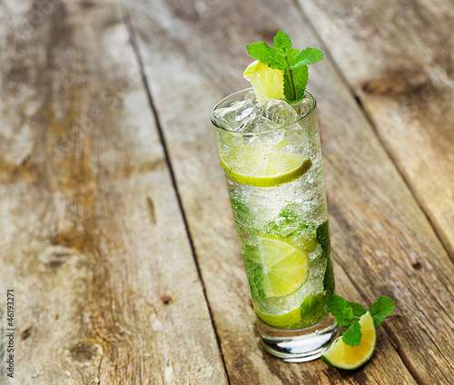 Mojito with a slice of lime on a wooden table