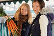 two young women buying carrots