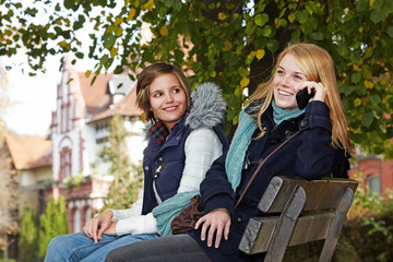 two young women sitting on a park bench