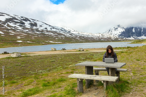Young girl working on a laptop among mountains
