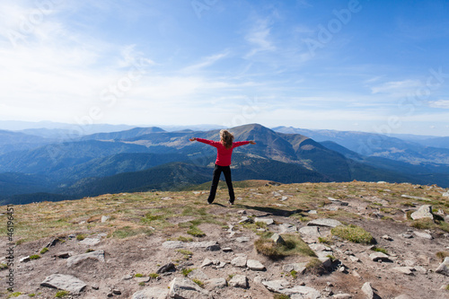 Hiker woman standing on mountain edge and looking to a sky