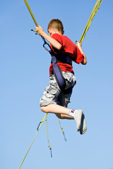 Little boy jumping on the trampoline (bungee jumping).