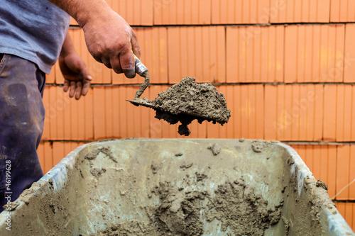 Maurer mit Ziegelhaus auf Baustelle