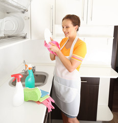 woman washing plate in kitchen
