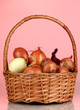 Ripe onions in basket on red background