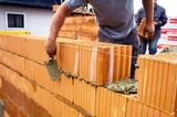 Maurer mit Ziegelmauer auf Baustelle