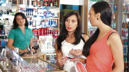 Women Testing Lip Gloss in Cosmetics Store