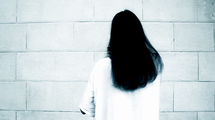 Mysterious woman with long black hair - horror concept