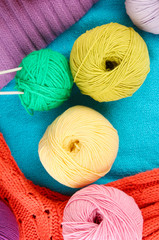 colorful wool sweaters and balls of wool close-up