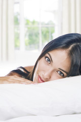 Portrait of young beautiful woman on white sheet