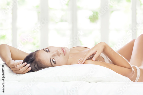 Portrait of young beautiful woman  in bed on color back