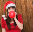 christmas woman blowing a balloon with her eyes crossed