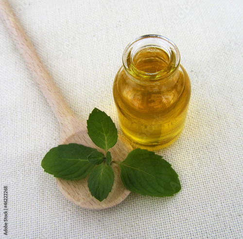 Bottle of peppermint oil with a wooden spoon, close-up