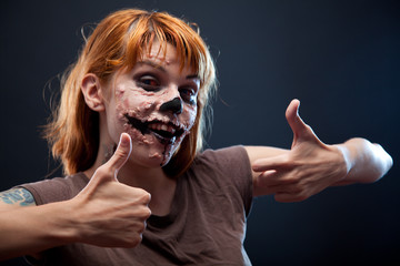 Happy zombie girl showing thumbs up