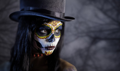 Sugar skull girl in tophat in the forest