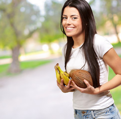 Young Girl Holding Banana And Coconut