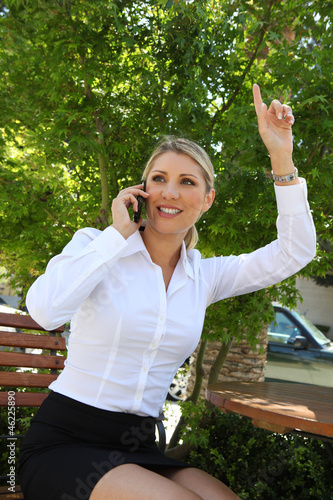 Blonde business woman waving for a taxi or to friend