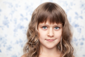 Portrait of sincere young grey-eyed girl child looking at camera