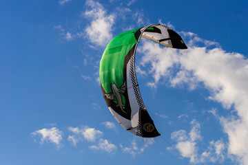 Big kite in the blue sky with some clouds