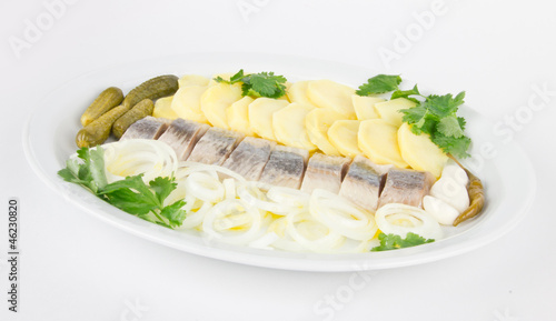 Portion of herring fish fillets with potato and onion