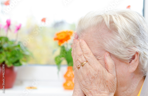 A crying elderly woman covering her face