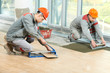Leinwanddruck Bild - Two tilers at industrial floor tiling renovation