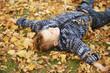 Kleiner Junge spielt im Laub