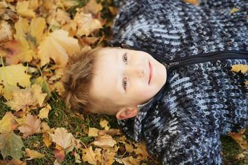 Junge liegt im Laub an einem Herbsttag