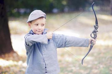 Junge spielt mit Pfeil und Bogen im Park
