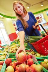 Frau greift nach Äpfeln im Markt