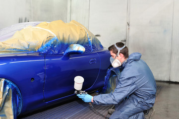 Worker painting a car in paint booth.
